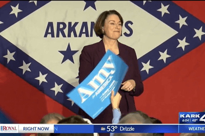 Klobuchar standing in front flags sold by FlagandBanner.com (KARK 4))