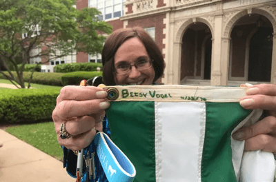 Betsy Vogel Boze shows where she sewed her name and the date she made the Earth Day flag now being flown at the school. (Photo: Jimmy Watson/The Times)