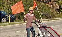 A pedestrian waves a flag while crossing a street. Courtesy St. Augustine Record