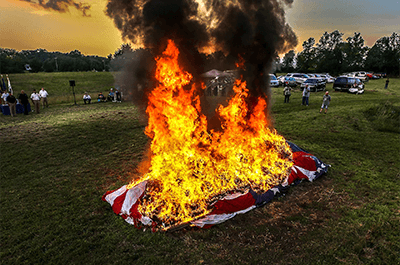 Thousands of American flags burn during a flag retirement ceremony by the Jeffersontown American Legion G.I. Post 244. Tens of thousands of American flags are under the large flag retired from Town & Country Ford. John Wright, with the post, believes that this flag retirement ceremony might be the largest in the U.S. June 29, 2019. (Photo: Michael Clevenger/Courier Journal)