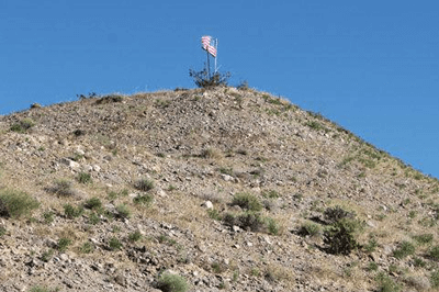 A lone American flag stands atop a mountain peak along Highway 95, JoANN SMITH, News West
