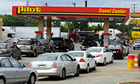 Cars line up at the Pilot Travel Center on Statesville Avenue to take part in a gas rebate offer through New Life Fellowship Center on Sunday afternoon. Pastor John P. Kee made the offer to church members during services, were given tokens to take to the station, and church paid $1 rebate for every gallon the members purchased. DAVID T. FOSTER III dtfoster@charlotteobserver.com