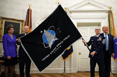 President Donald Trump stands as Chief of Space Operations at US Space Force Gen. John Raymond, second from left, and Chief Master Sgt. Roger Towberman, second from right, hold the United States Space Force flag as it is presented in the Oval Office of the White House, May 15, 2020, in Washington. Secretary of the Air Force Barbara Barrett stands at far left.  ALEX BRANDON/AP