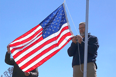 Jamie Popwell, right, attaches an American flag to a new flagpole he put up on Wednesday along Lee Road 721 in Beauregard. Kara Coleman Fields/kcoleman@oanow.com